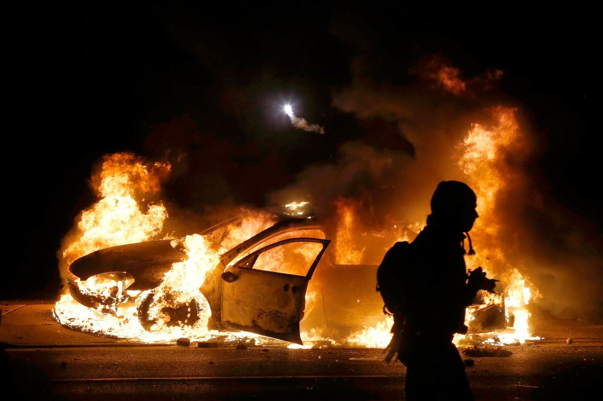 A police car burns on the street after a grand jury returned no indictment in the shooting of Michael Brown in Ferguson, Missouri