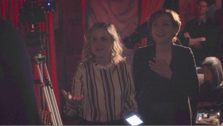 Комедийная звезда Эми Полер держит в своих руках Passport в кинофильме «Очень Мюреевское Рождество» телеканала Netflix.