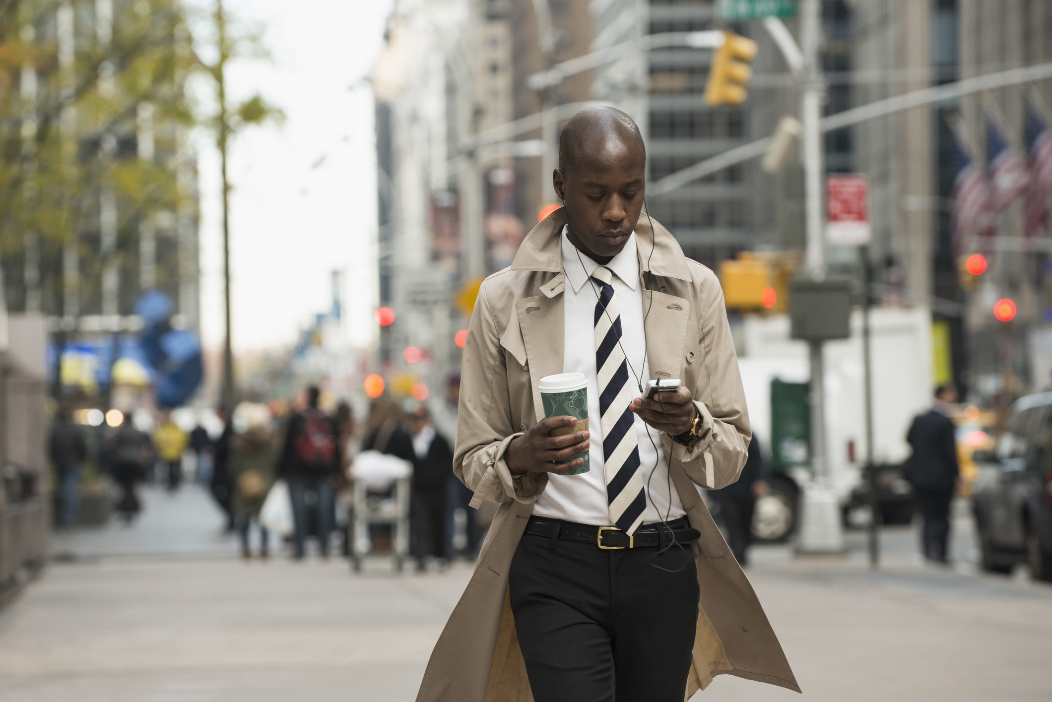 Black businessman using cell phone on city street