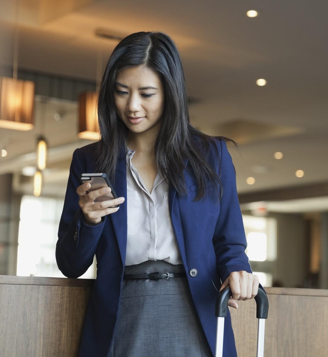Businesswoman using smart phone in hotel lobby